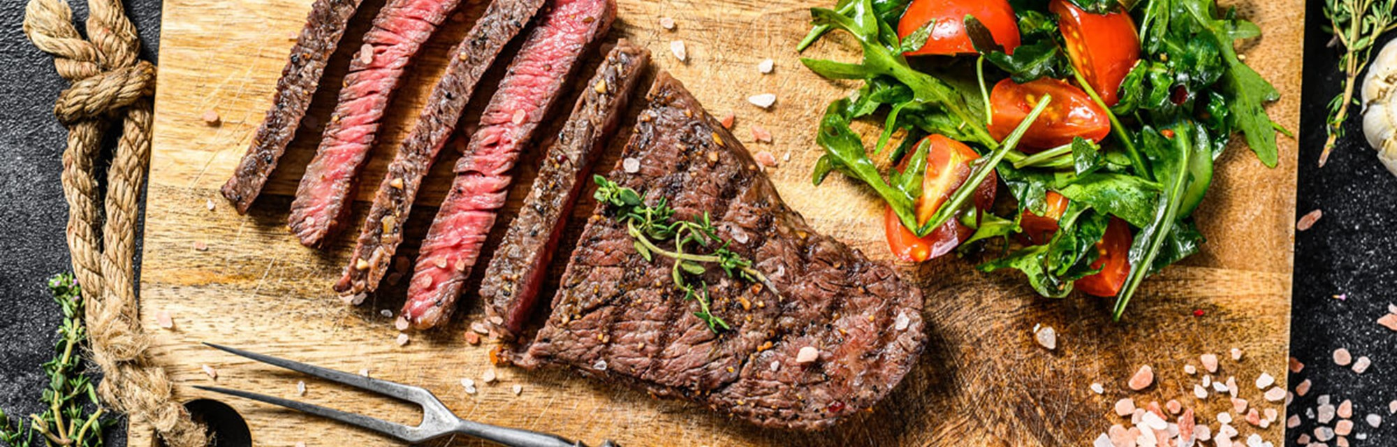 Medium-rare rump steak on a chopping board with cherry tomatoes and leafy salad